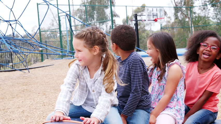 Elementary school kids spinning in a playground Royalty-Free Stock Footage #1017044569
