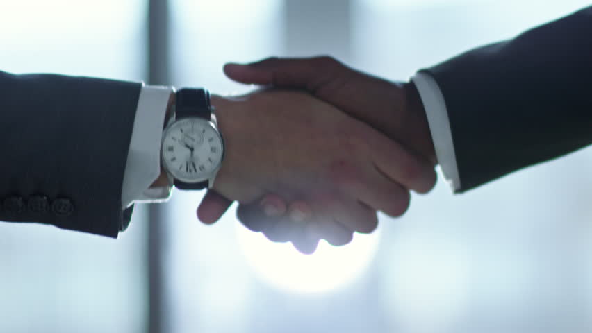 Close up shot of two unrecognizable businessmen in formalwear shaking hands in office, shot against the sun