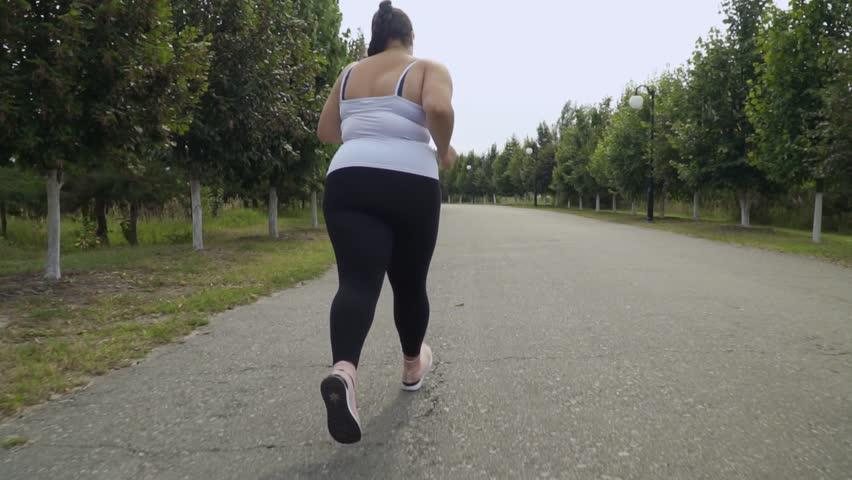 Fat girl runs along the road   Shutterstock HD Video #1017060502