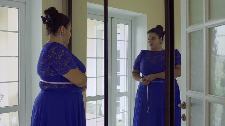 Fat girl in a blue dress in front of a mirror