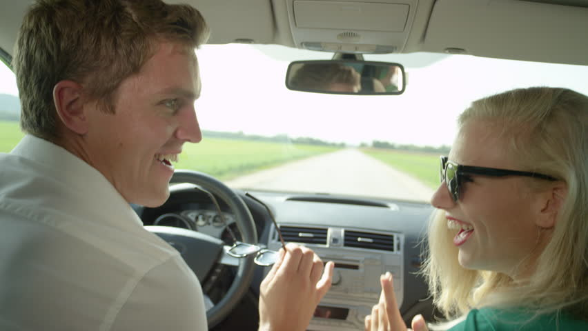 SLOW MOTION, CLOSE UP: Cheerful young Caucasian couple dancing during their drive through the scenic countryside. Girlfriend and boyfriend having fun during their road trip on a beautiful sunny day. #1017063247