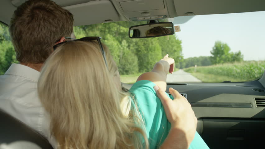 SLOW MOTION, CLOSE UP: Happy woman in her boyfriend's embrace points towards the distance as young couple in love drives down the scenic rural road. Tourist man and woman cuddling during road trip. #1017063289