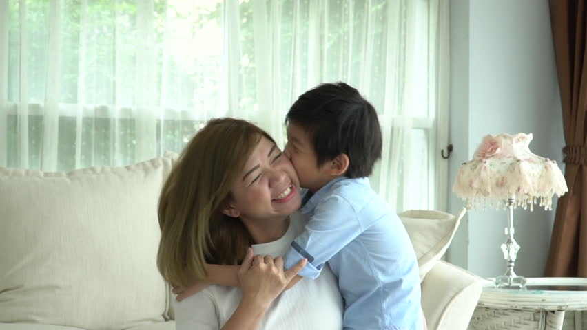 Asian child on a piggy back ride with his mother at home slow motion #1017079765