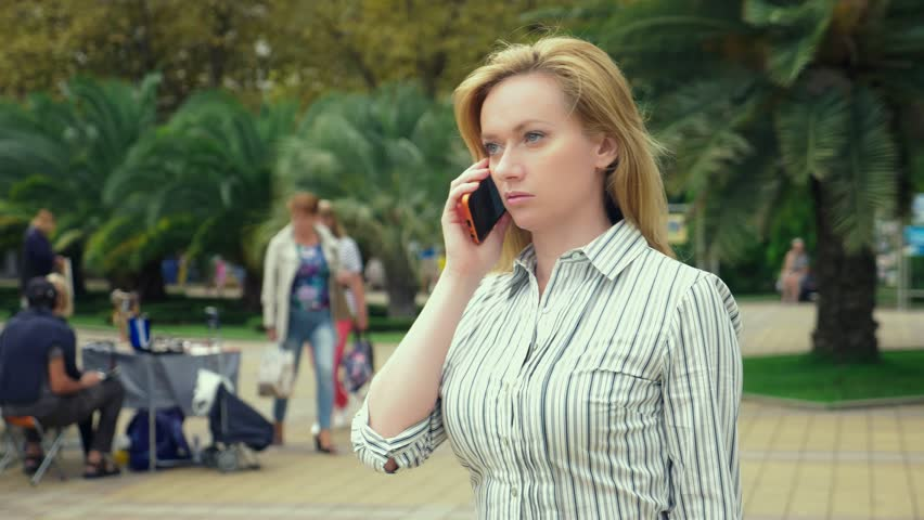 Woman blonde is talking on the phone on the run, she is in a hurry. outdoors in summer. slow-motion
