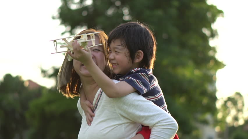 Cute Asian mother and son playing wooden airplane together in the park outdoors slow motion
