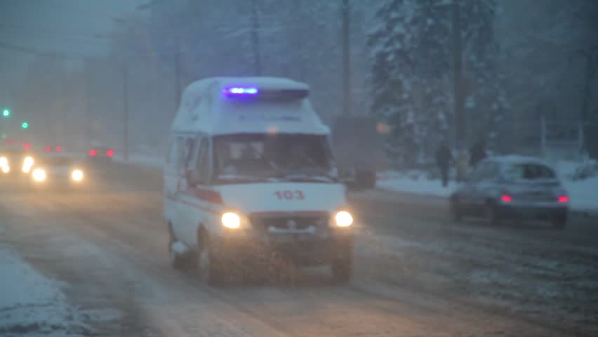 Snowfall. the ambulance rides along the snow-covered street. occurrence in the evening. bus stop in winter. pedestrians in the metropolis. traffic jams in the city. The snowfall paralyzed traffic in t
