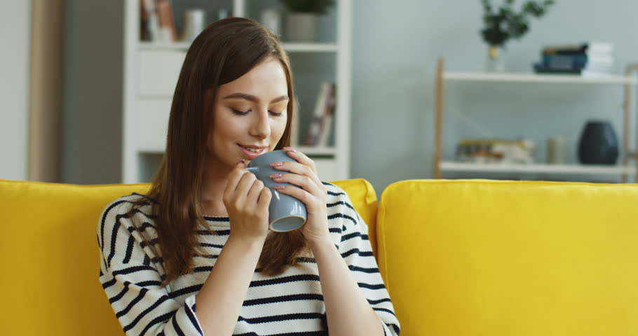 Portrait of the young Caucasian good looking woman drinking coffee or tea and smiling while sitting on the couch at home.