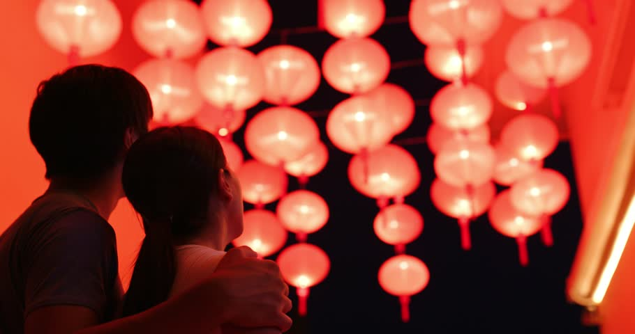 Couple enjoy looking at the red lantern at night