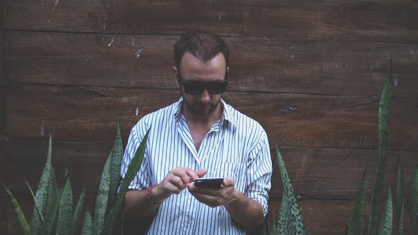 Man using cellphone in the garden. | Shutterstock HD Video #1017173203