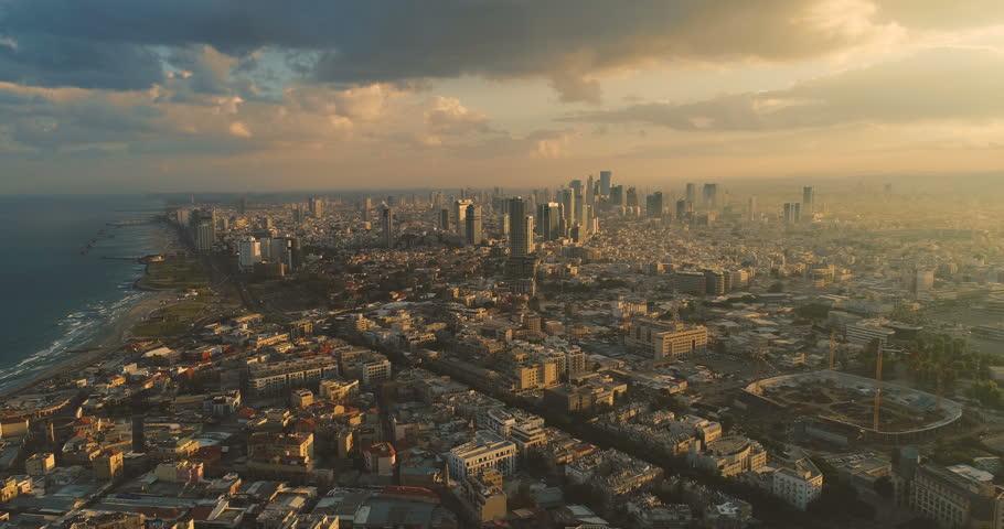 Tel Aviv Skyline from Drone. Aerial shot long super wide horizon view. Sunset orange Sky coastline and office building in a modern Tel Aviv