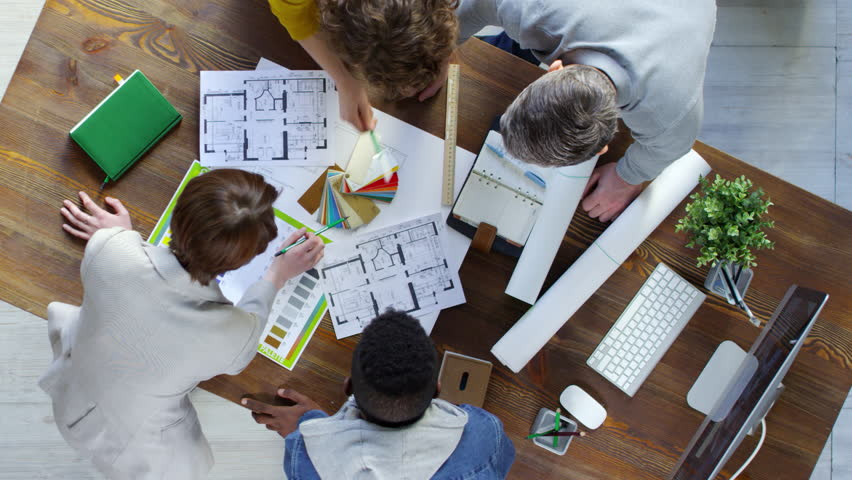 Top view of group of four creative people using floor plans and color palettes when choosing apartment design ideas in office | Shutterstock HD Video #1017224404
