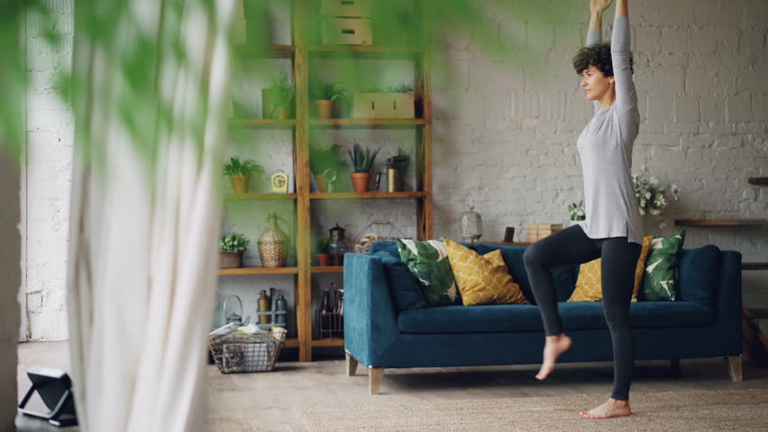 Active person is doing yoga at home practising balance exercises on one leg standing on floor alone. Beautiful loft style flat with furniture and plants is visible. | Shutterstock HD Video #1017224998