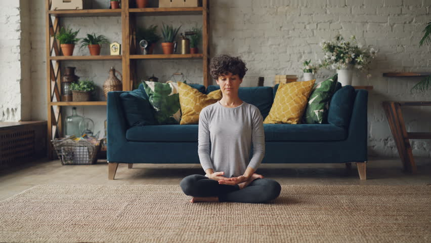 Zoom-in portrait of attractive girl in sports clothing sitting in lotus position with hands in namaste then putting hands on knees, breathing and resting. | Shutterstock HD Video #1017225010