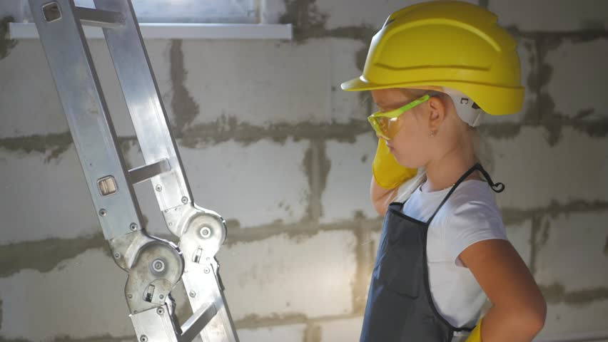 Childhood, construction, architecture, building and people concept - smiling little girl in protective yellow helmet and safety glasses with brush for paint | Shutterstock HD Video #1017233770