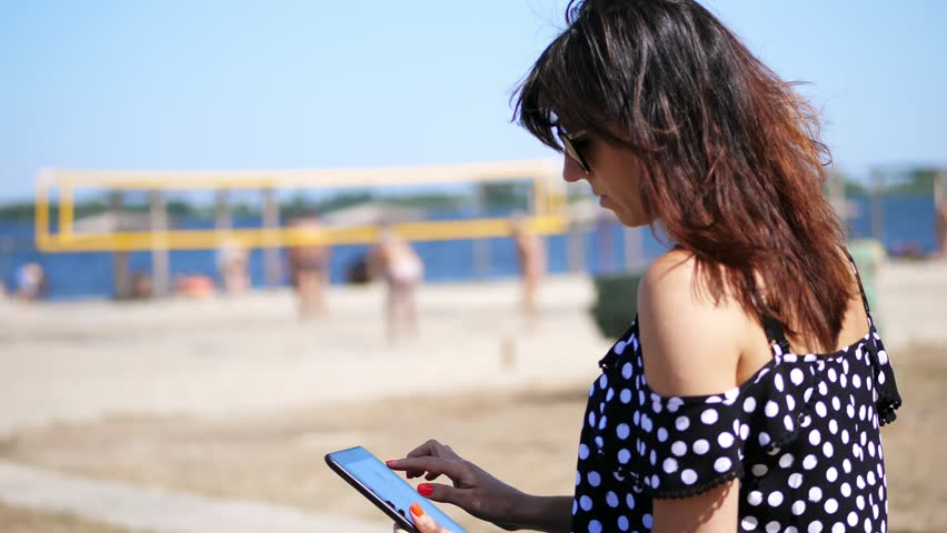 Portrait, beautiful girl in sun glasses working on a tablet, on the beach, on a hot summer day, against a background of beach volleyball | Shutterstock HD Video #1017250279