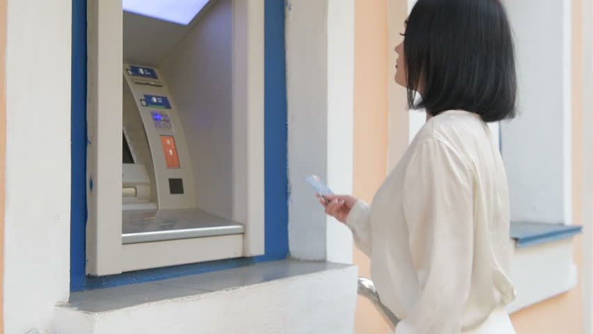 Attractive young business woman is inserting a credit card to withdraw some money. | Shutterstock HD Video #1017250402