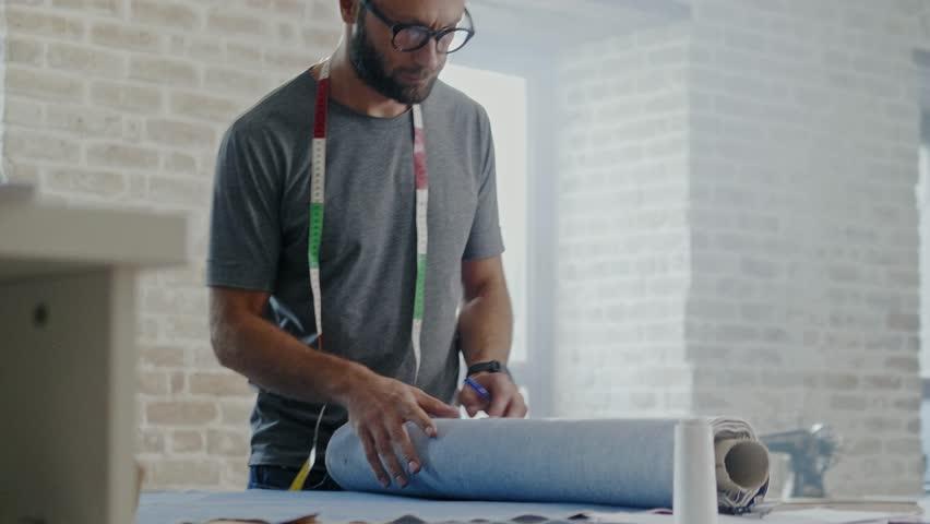 Fashion designer working in his studio #1017262573