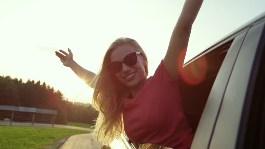 SLOW MOTION, LENS FLARE, CLOSE UP: Happy Caucasian girl outstretches her arms while sticking out the car window. Carefree blonde woman driving through the idyllic countryside on a beautiful morning. #1017265669
