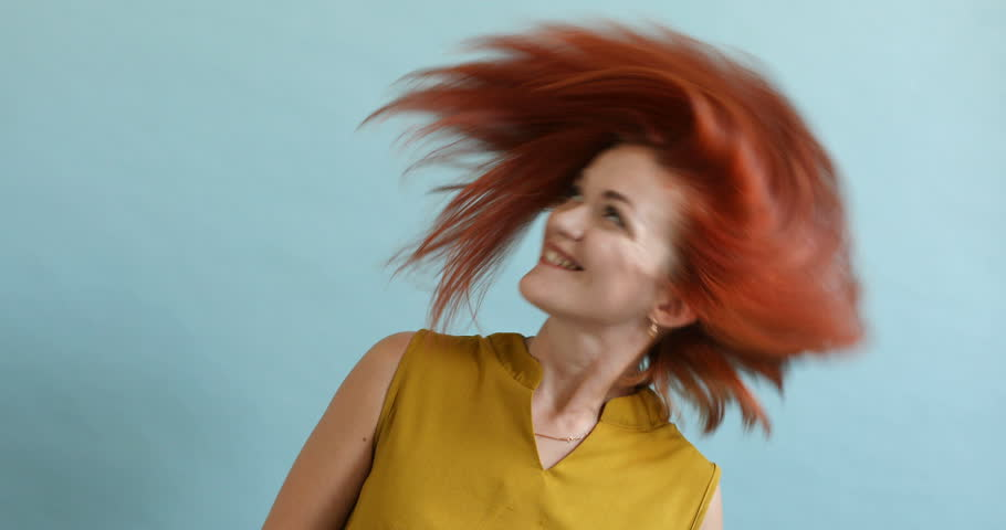 Portrait of a happy girl in studio on a blue background. She is waving her head, and her long chestnut hair is fluttering. Studio stock video of a red-haired woman with long flowing  | Shutterstock HD Video #1017279865