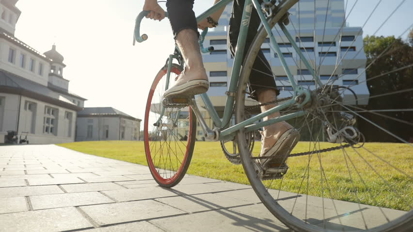 Man in light brown trainers going cycling near huge university facilities, outdoor low angle shot on lovely monday morning Royalty-Free Stock Footage #1017292597