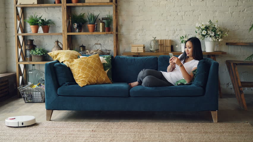 Attractive Asian girl is enjoying modern technology using smartphone and robotic vacuum cleaner sitting on sofa at home. Innovations and interiors concept. | Shutterstock HD Video #1017293209
