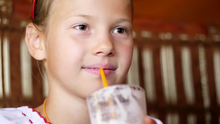 Happy smiling teen girl child drinks a milkshake in cafe. she is dressed in Ukrainian national clothes, embroidery, vishivanka | Shutterstock HD Video #1017297667