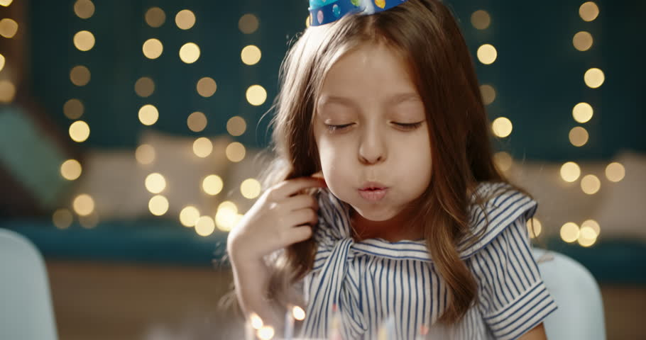 Kid having birthday. Cute little girl maling a wish, then blowing out the candles on bithday cake during party - happy childhood concept 4k | Shutterstock HD Video #1017320740