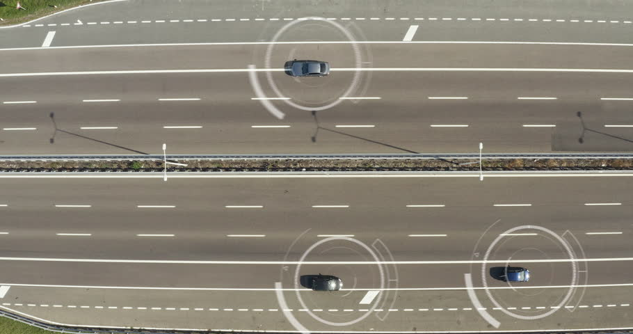 Aerial view of a highway where cars pass to go to the city and a futuristic graphic appears. Concept of: speed control, espionage, satellite control, connection.