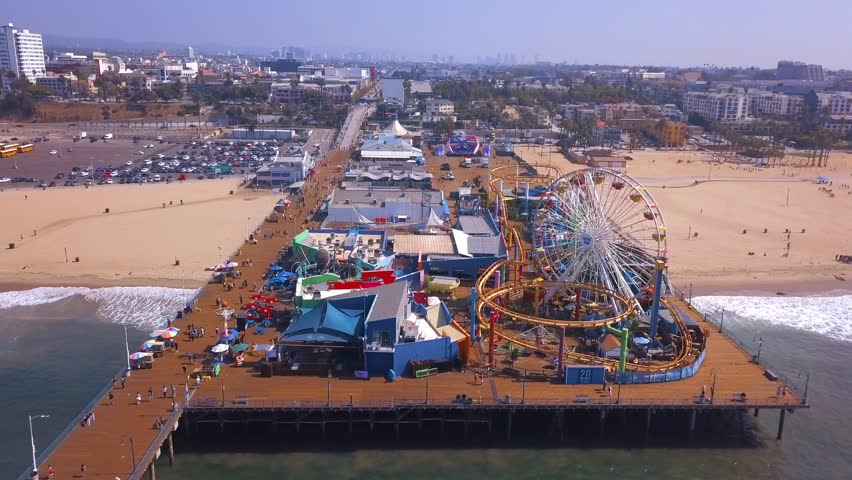 Early morning aerial view of the Santa Monica pier during a sunny day with amusement park view and people walking around in Los Angeles. | Shutterstock HD Video #1017332584