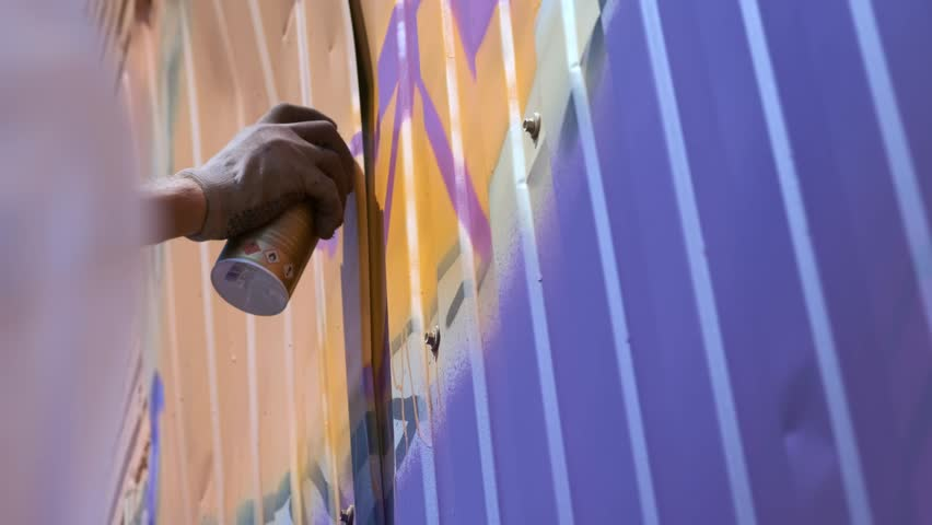 A young guy with a can of paint draws graffiti on the wall. One hand close-up