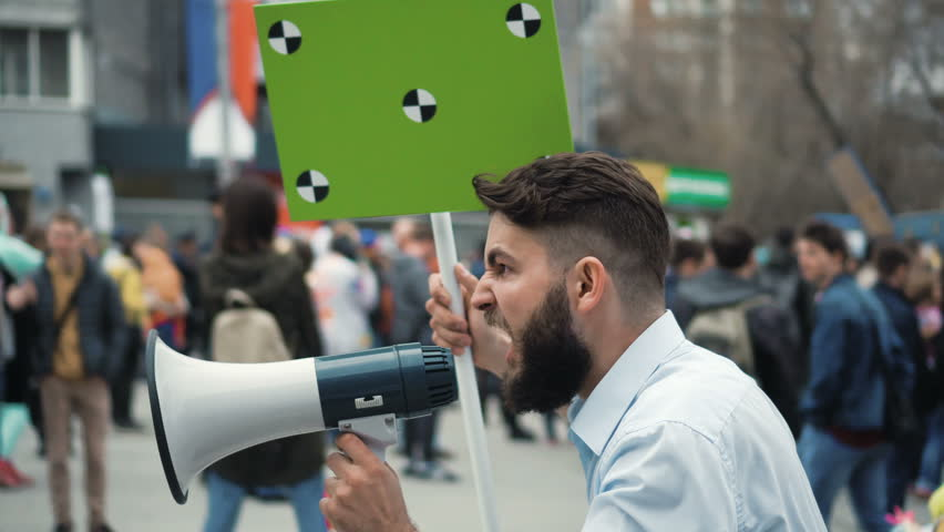 Angry adult young man with a banner in hands go and shouts loudspeaker rally. Aggressive protester on strike. Revolution in city during day. Crowd people in the background on street. 20s caucasion boy | Shutterstock HD Video #1017342052