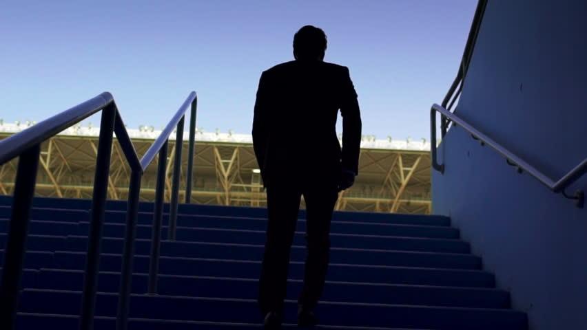 Businessman walking in Empty seats in a stadium