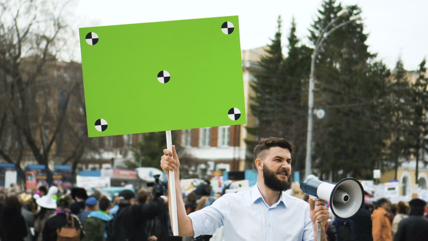 Angry adult young man with a banner in hands go and shouts loudspeaker rally. Aggressive protester on strike. Revolution in city during day. Crowd people in the background on street. 20s caucasion boy | Shutterstock HD Video #1017353236