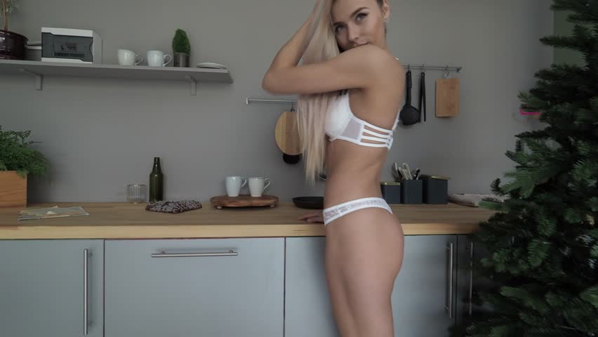 Beautiful young white blond woman in white lingerie playing hair next to window at studio. New year eve. Middle shot. Happy and smiling. Slow motion. Xmas Tree #1017355780