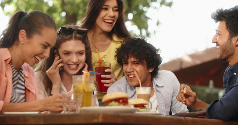 Five multiethnic friends sitting at table in cafe, talking on phone with someone, and laughing. People enjoying theit time together 4k | Shutterstock HD Video #1017373783
