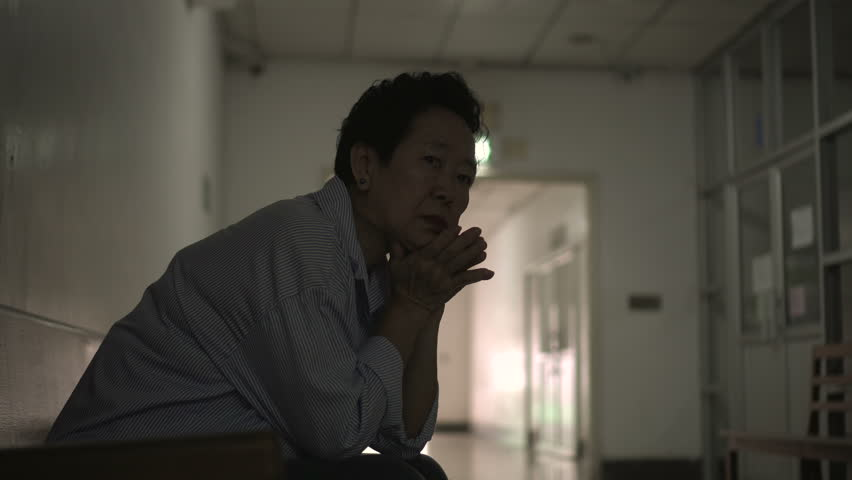 Asian senior elder woman waiting at hospital corridor worry and sad