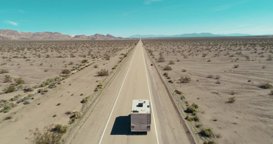 AERIAL - A drone follows a brown camper van from the back in the middle of the Mojave Desert and slowly gets closer to the van on route 66 on a clear blue day.
