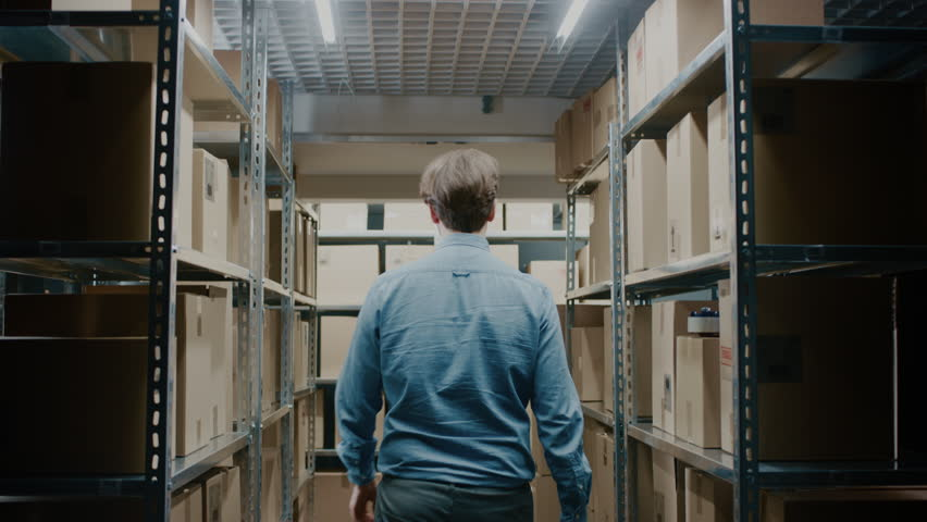 Worker Walks Through Warehouse Storeroom with Rows of Shelves Full Cardboard Boxes, Parcels, Packages Ready For Shipment. Shot on RED EPIC-W 8K Helium Cinema Camera. #1017422680