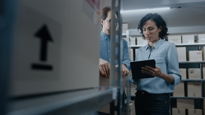 Female Inventory Manager Shows Digital Tablet Information to a Worker Holding Cardboard Box, They Talk and Do Work. In the Background Stock of Parcels with Products Ready for Shipment.  | Shutterstock HD Video #1017422734