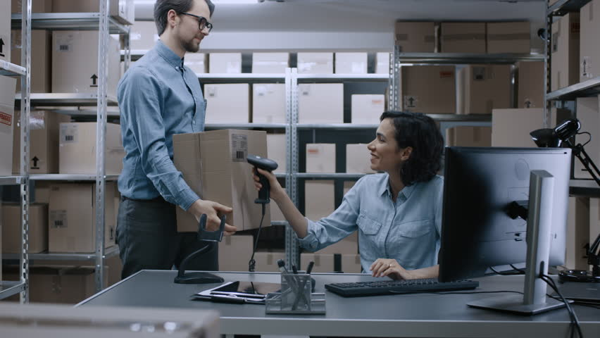 Female Inventory Manager Scans Cardboard Box with Barcode Scanner, Worker Puts Package on the Designated Shelf. In the Background Rows of Cardboard Boxes with Products Ready For Shipment.  Royalty-Free Stock Footage #1017422818