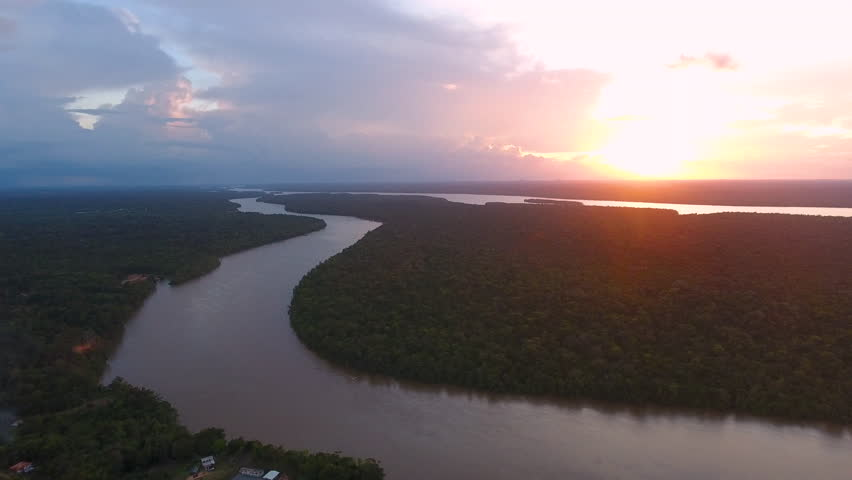 Flying over Mana river Guiana Suriname during sunset. Amazonian forest