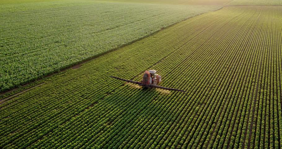 Aerial drone shot of a farmer spraying soybean fields #1017454060