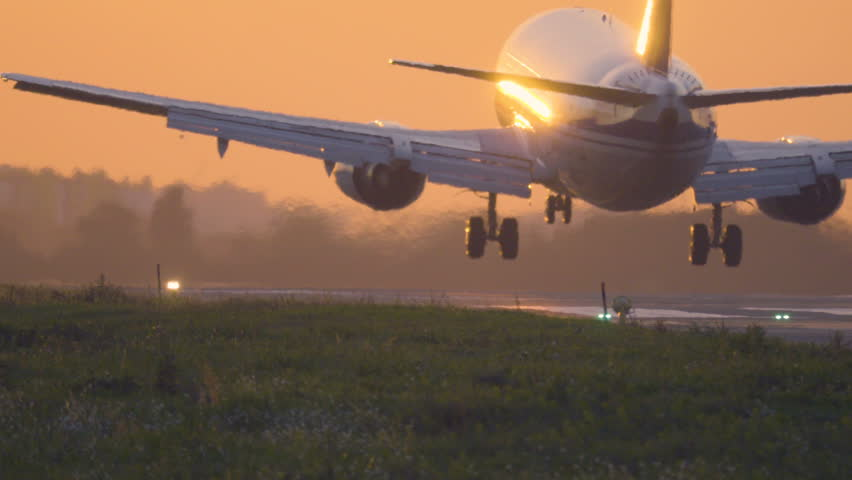 Airplane is landing to the runway at sunset. Back view