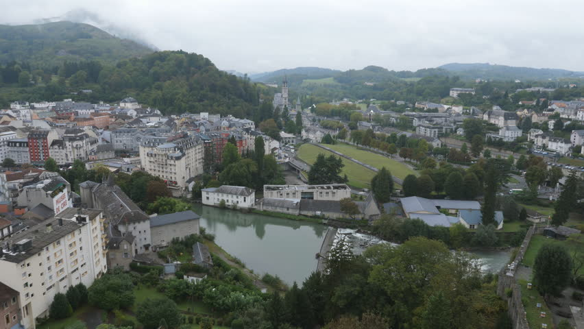 Aerial view of town of Lourdes, France. Sanctuary of Our Lady of Lourdes, also known as the 'Domain' in the distance. Handheld shot with stabilized camera. | Shutterstock HD Video #1017461035