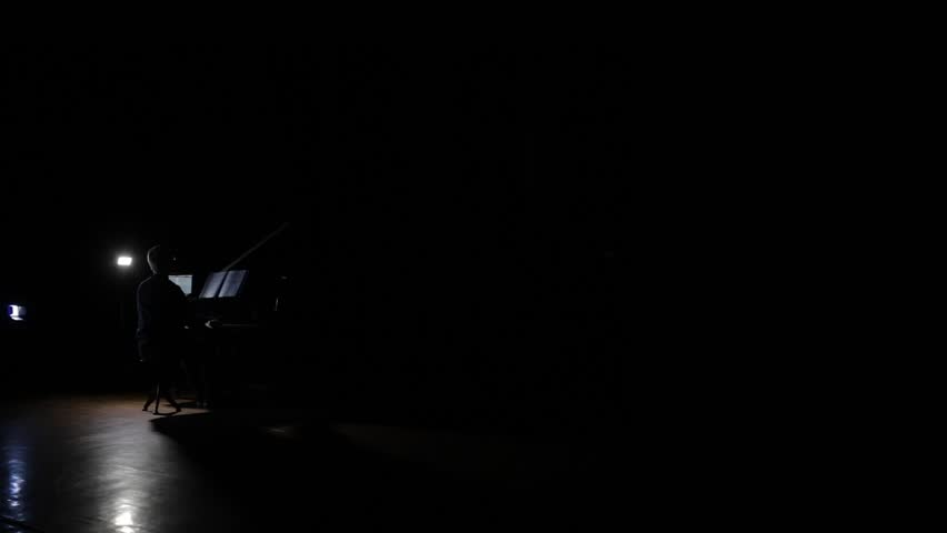 Young man playing on grand piano in the total darkness. Music scores and laptop are on grand piano. | Shutterstock HD Video #1017479101