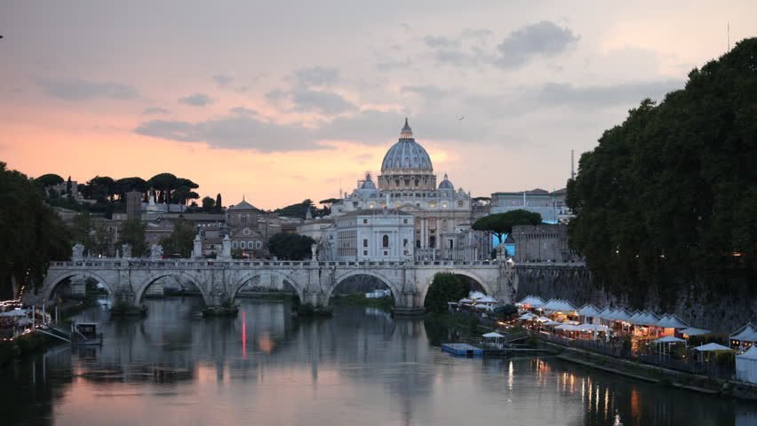 ROME, ITALY - AUGUST 14, 2018: Time lapse of traffic on St. Angelo bridge against St. Peter's Basilica in evening. The historical center of Rome is listed as UNESCO World Heritage since 1980   Shutterstock HD Video #1017488809