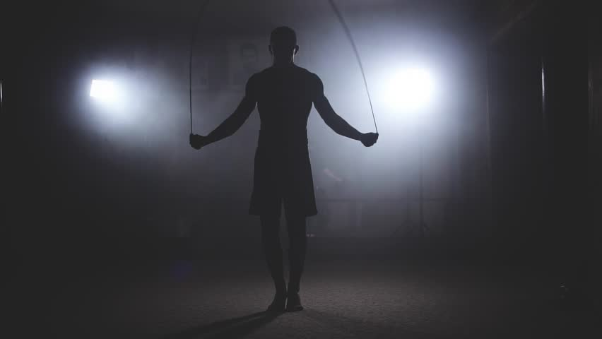 Boxer does some jump rope exercises in dark room under light. Fighter training in smoky studio in slow motion. Silhouette on dark background