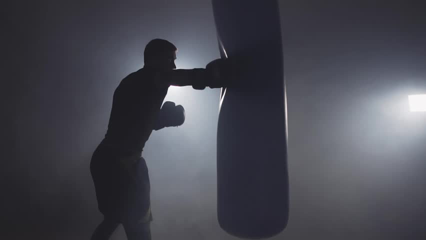 Alone boxer hits punching bag in dark gym in slow motion. Young man training indoors. Strong athlete in gym. Sport concept. Medium shot. Sportsman boxing in smoky studio