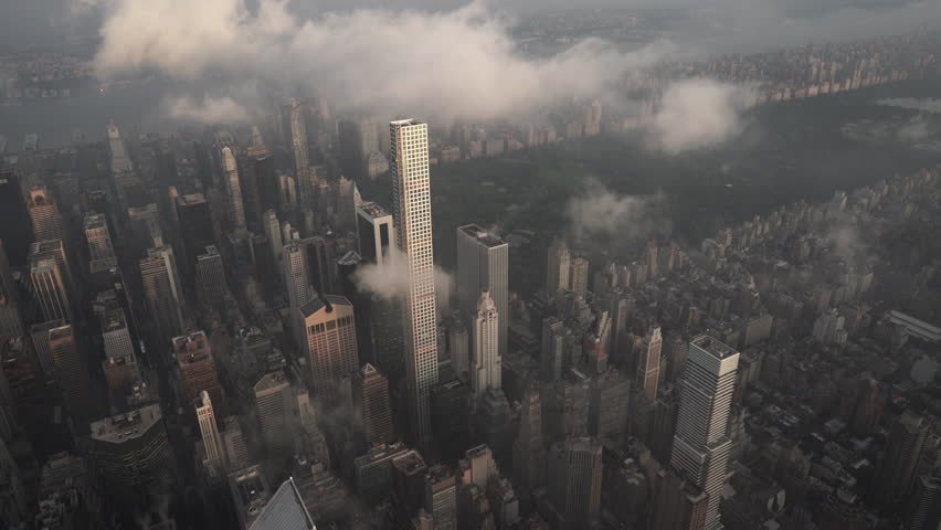 New York City Circa-2015, aerial view flying over Midtown Manhattan skyscrapers toward Central Park at sunrise, with fog and low level clouds at sunrise