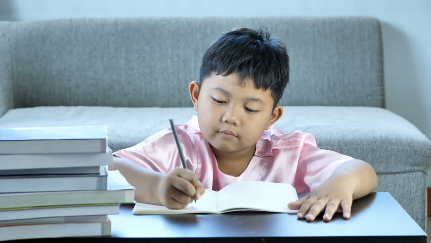 Cute little boy asian write into book, Happy smile at home. education concept  | Shutterstock HD Video #1017520930